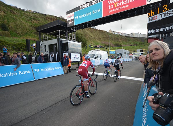 The cyclists crossing the finish line in Scarborough