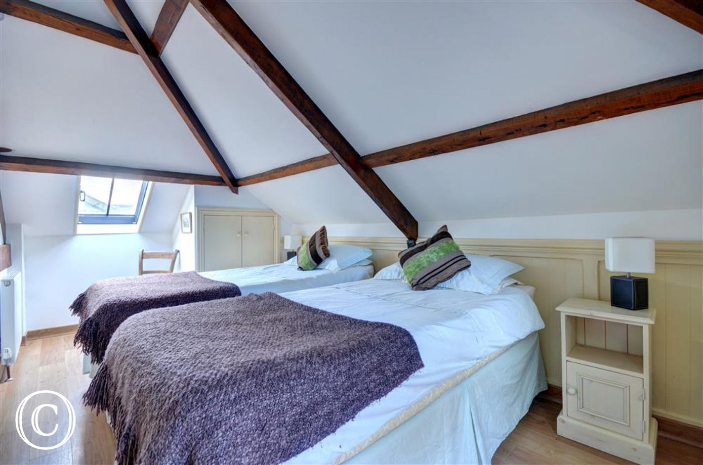 Lovely beamed ceiling and twin beds.