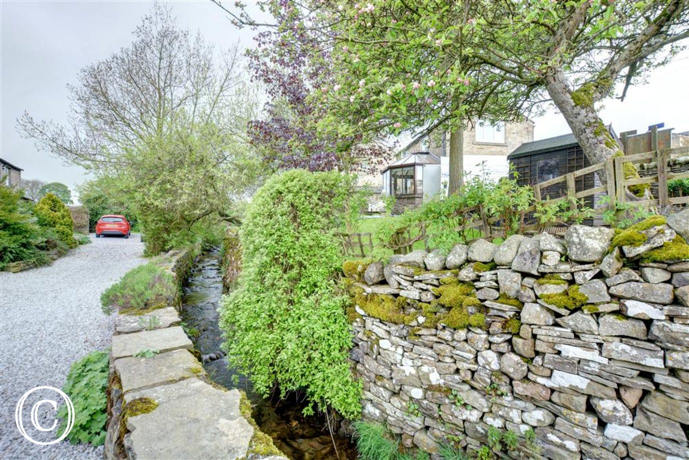 The stream over the stone wall at the bottom of the garden