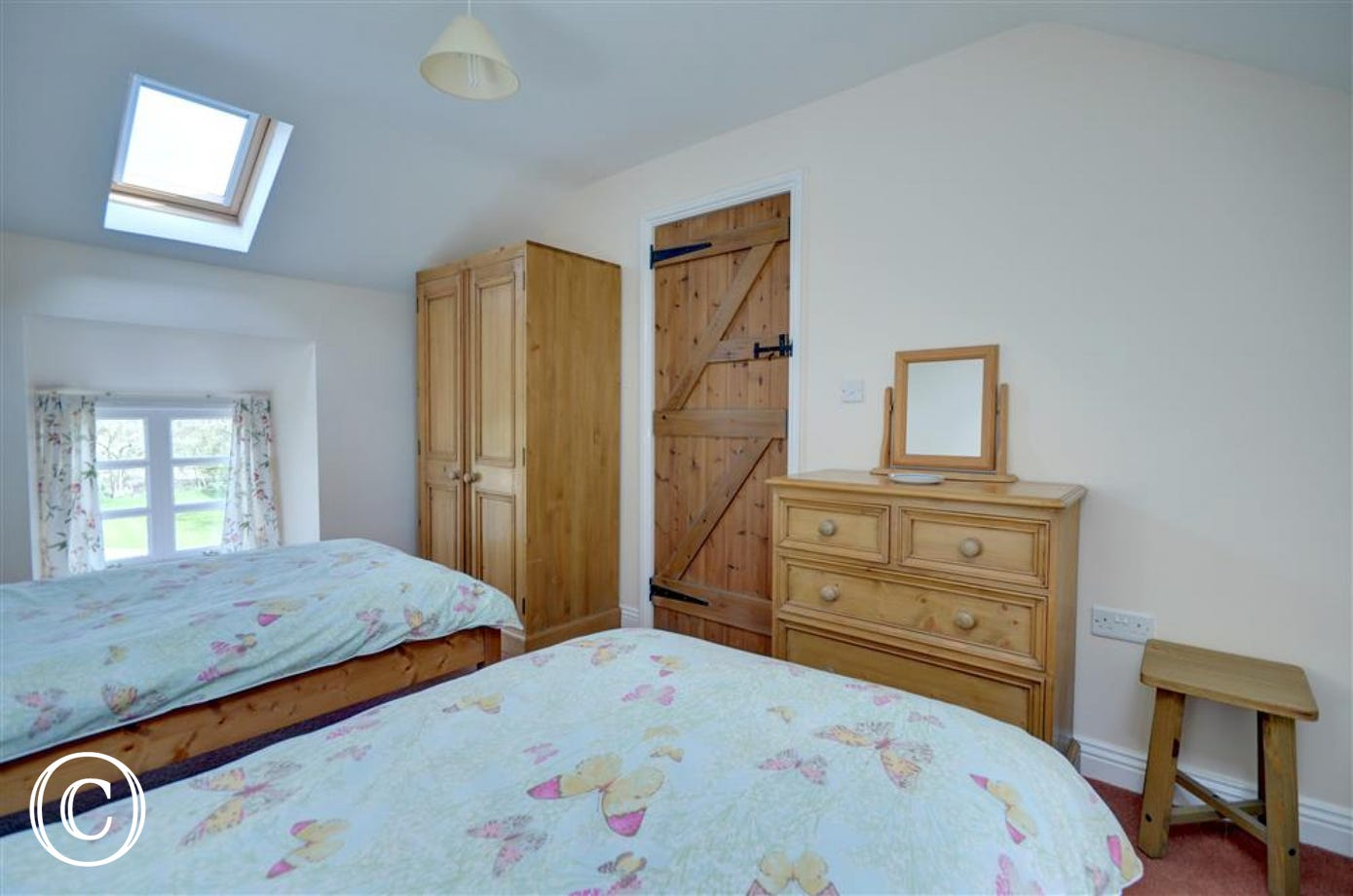 Twin beds with wardrobe and chest of draws.