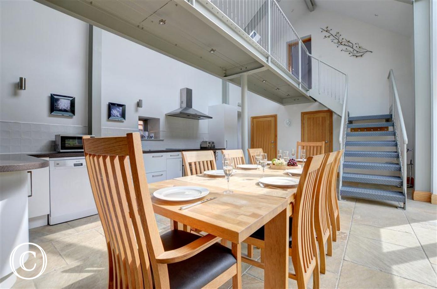 A the dining area sits undernesth a bridge between the upstairs bedrooms.