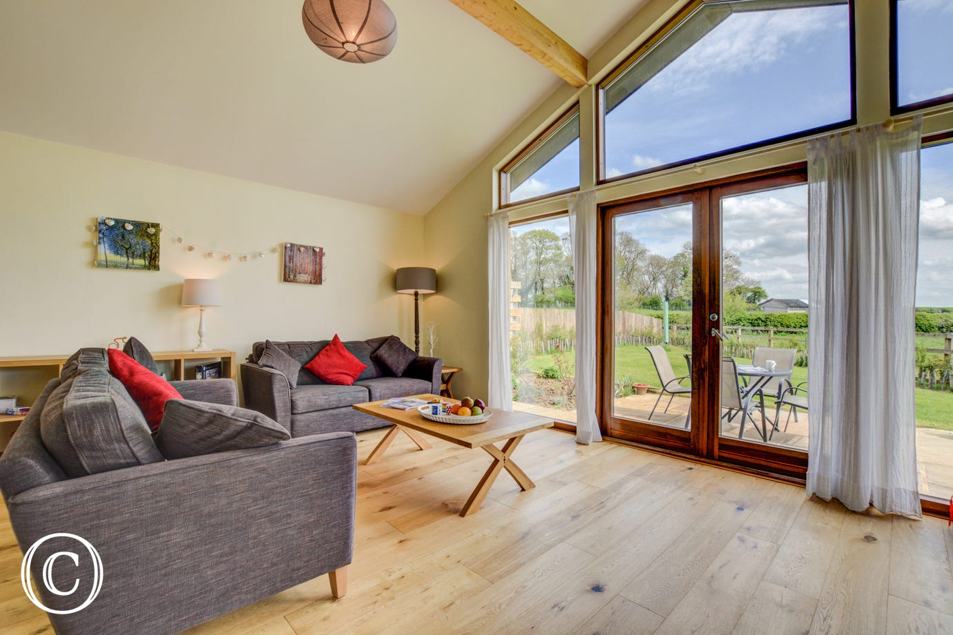 The spacious open plan living area with french windows leading onto the garden, views over the stunning countryside