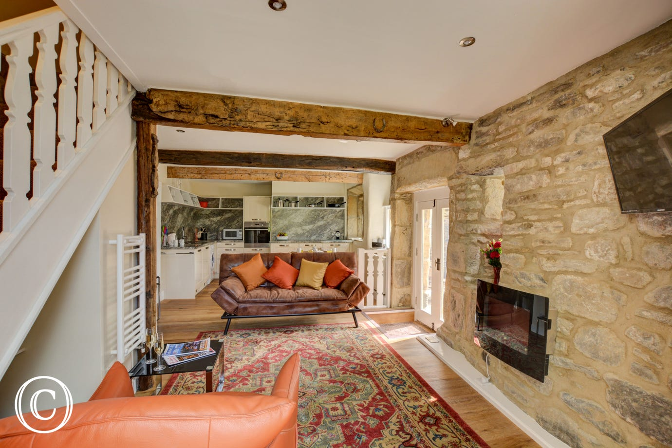 Open plan living area, with exposed stone walls, comfortable seating and well equipped kitchen