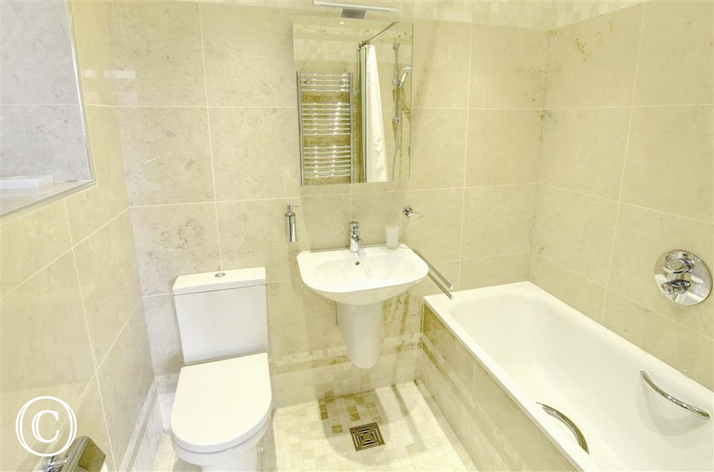 En-suite bathroom with a bath and shower over the bath.