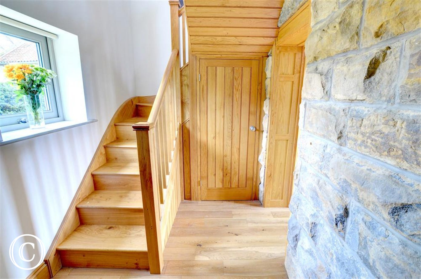 Hallway has open stone wall and beautiful solid wood stairs.