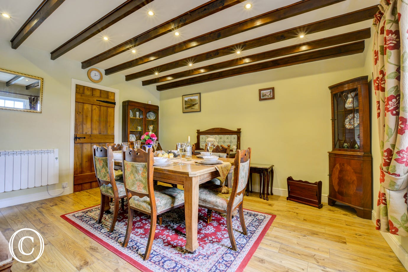The spacious dining room with beamed ceiling and wood flooring
