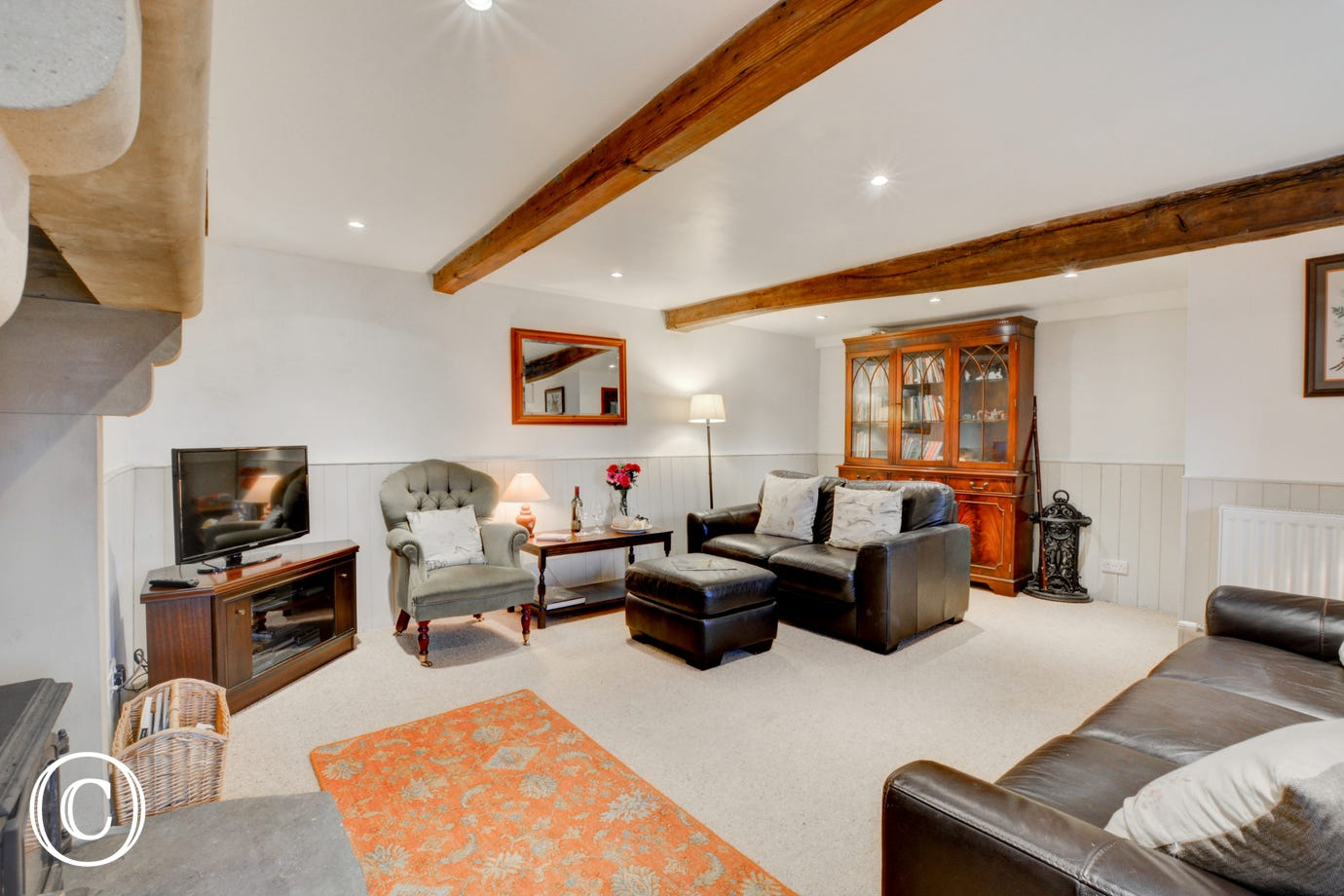 Spacious lounge with beamed ceiling and solid fuel stove