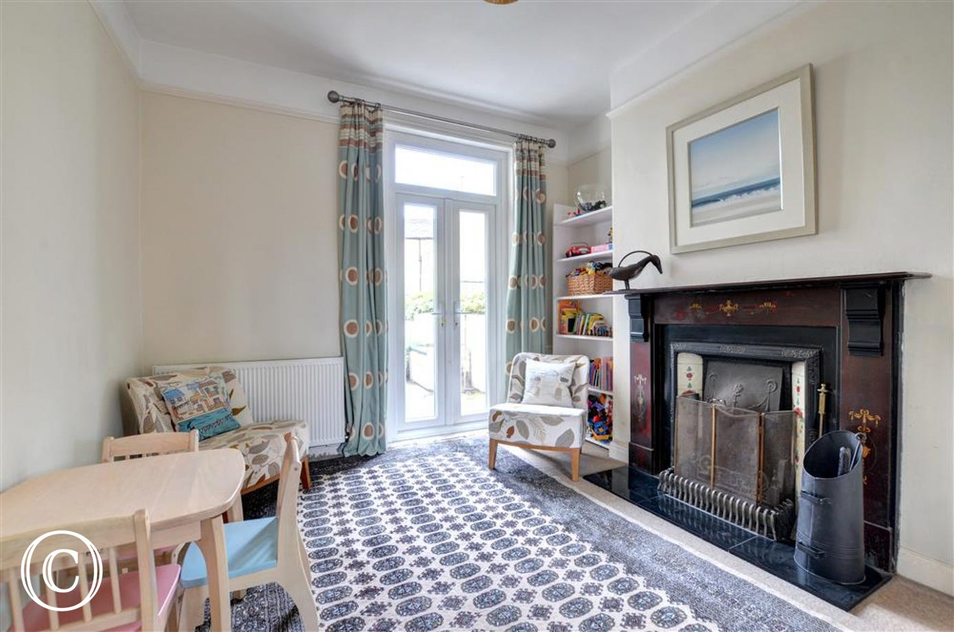 This Sitting Room can double as a children's playroom. It has French doors which lead out to the rear Garden area.