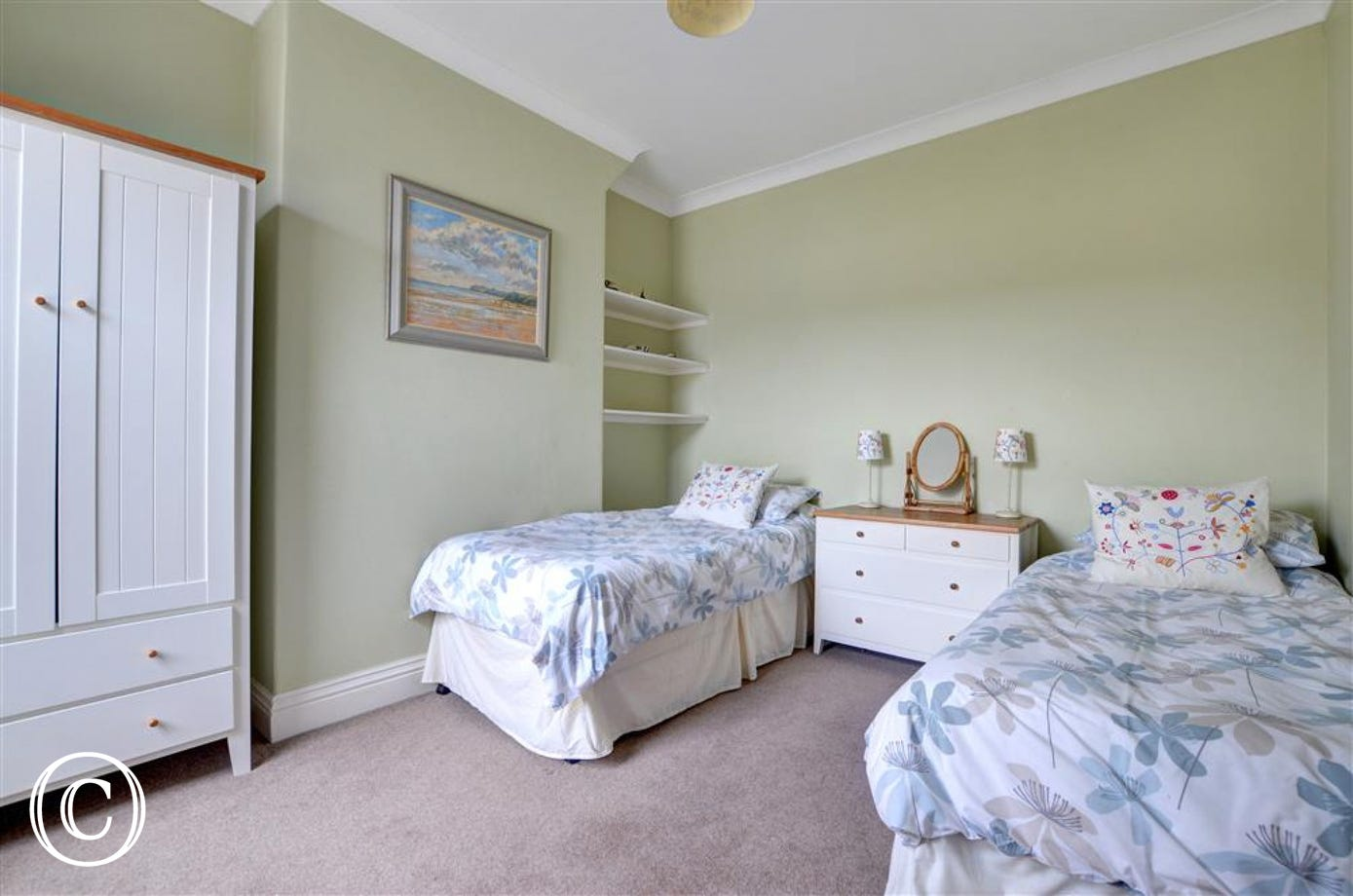 This twin Bedroom has a chest of drawers and wardrobe for storage.