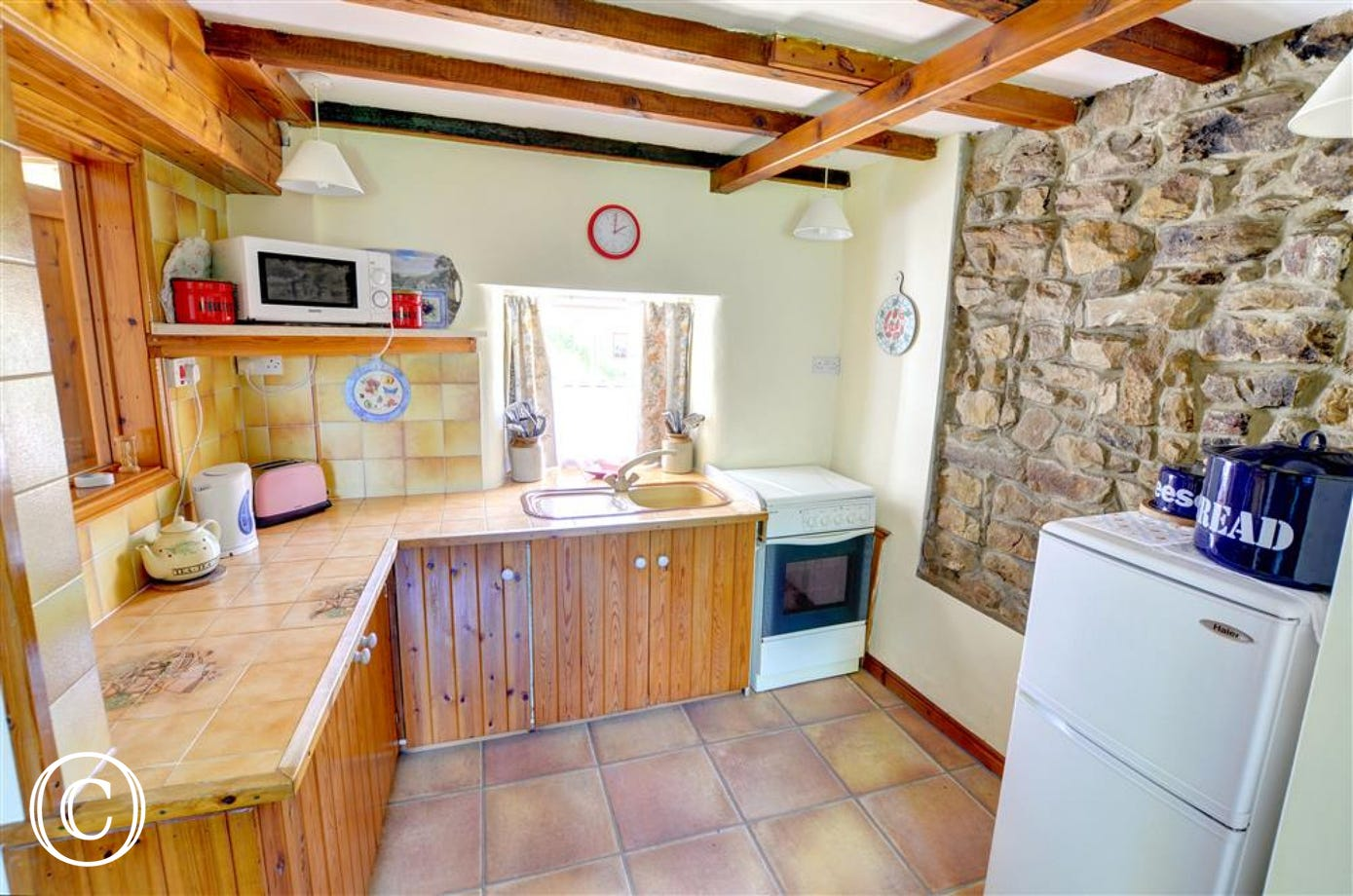 The Kitchen area is an open plan space off the Lounge which retains traditional features including a beamed ceiling and exposed stone wall.