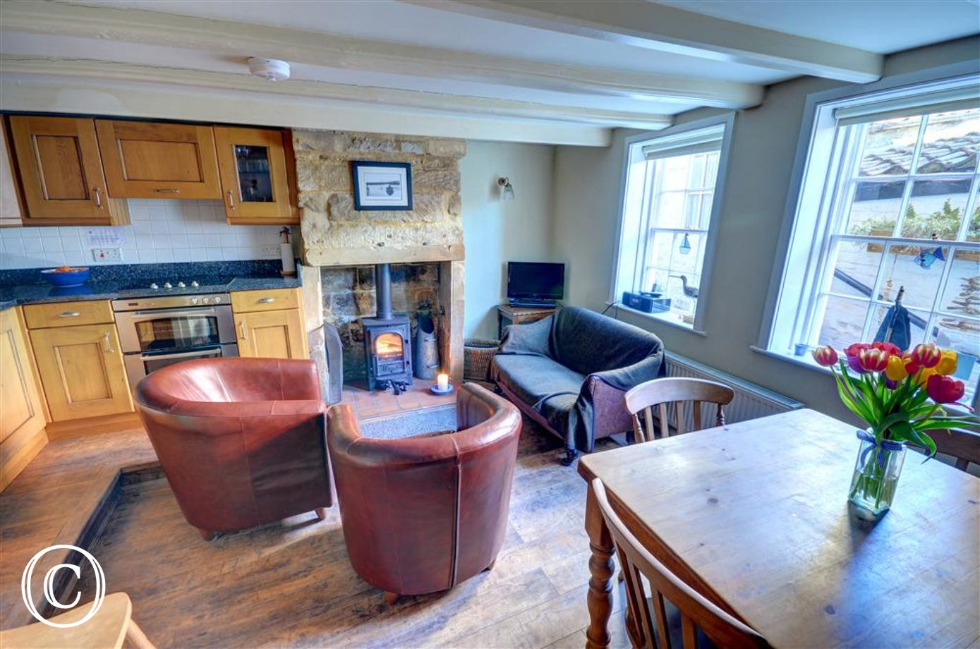 Lounge/Diner with Inglenook fireplace, woodburner and wooden table and chairs.