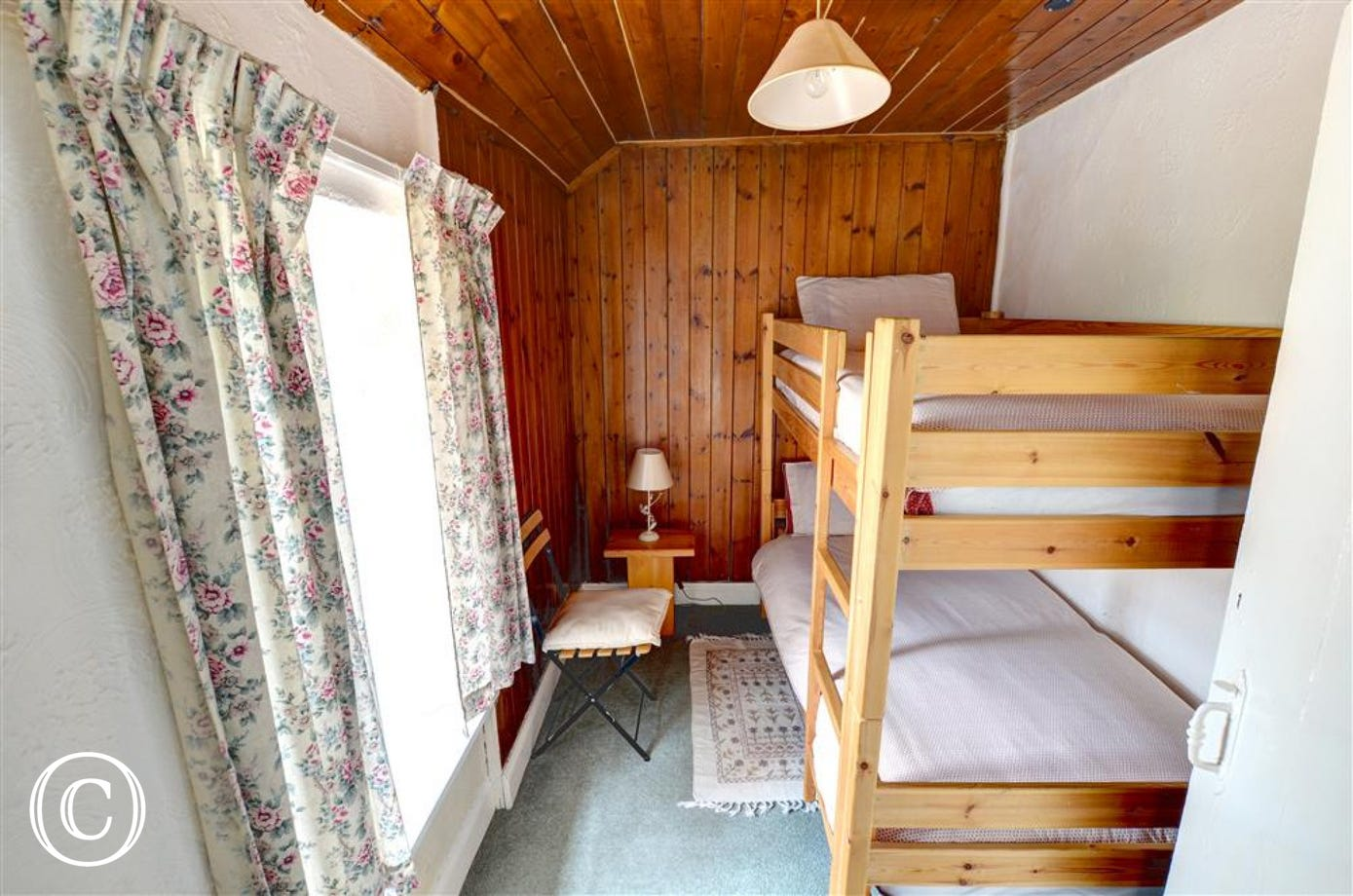Twin Bedroom with bunk beds and a chest of drawers behind the door.