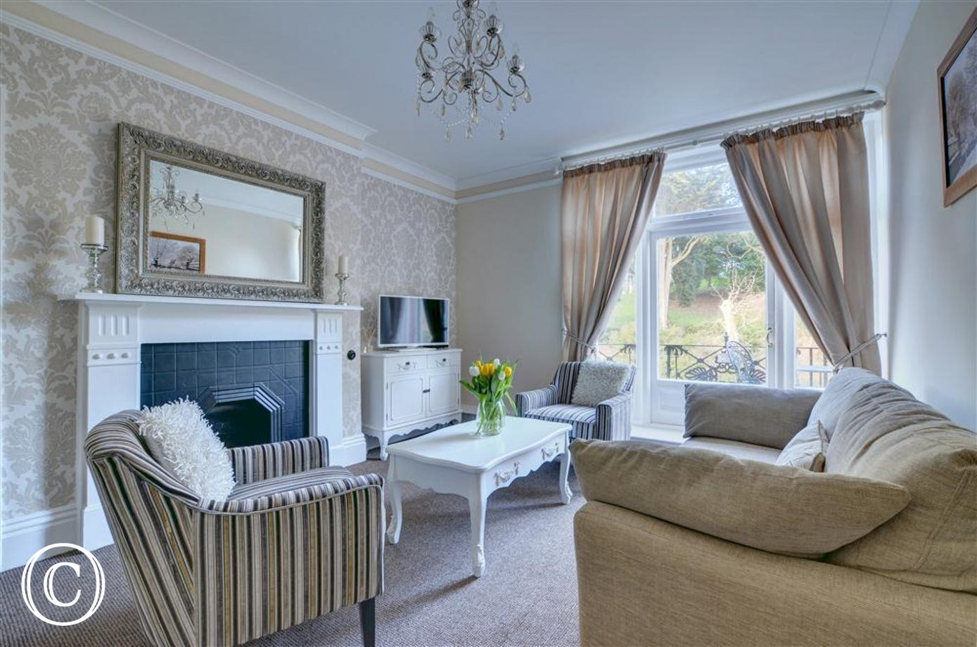 Spacious lounge with comfortable sofas, views over Pannett Park and access to the balcony.