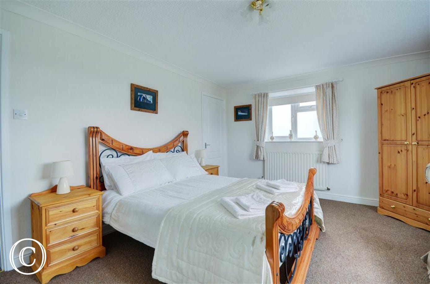The main bedroom has a double bed and a chest of drawers.