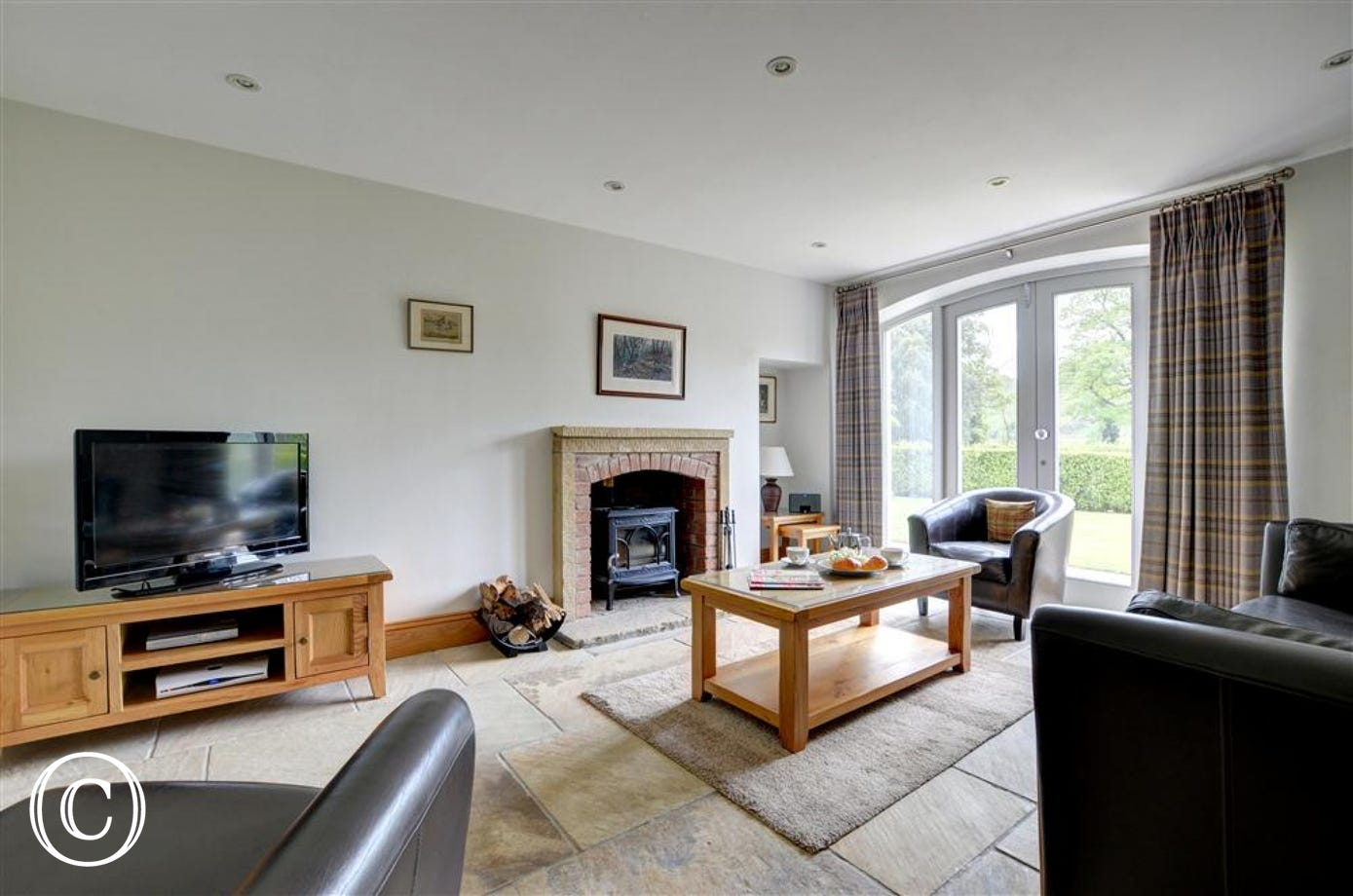 Separate lounge with woodburner and French doors.