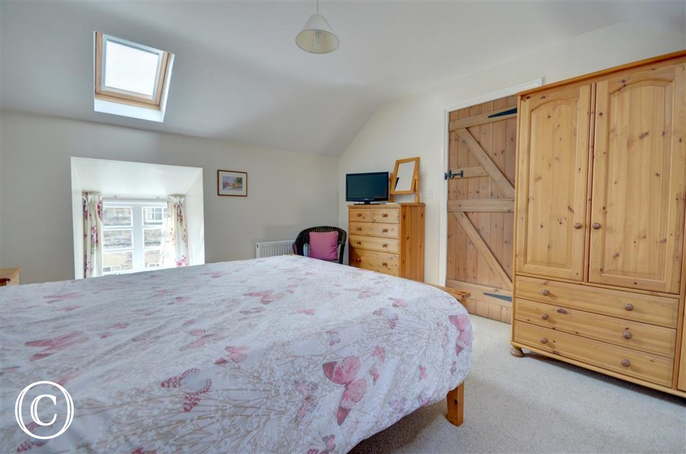 King size bed with wardrobe and chest of draws and Freeview TV.