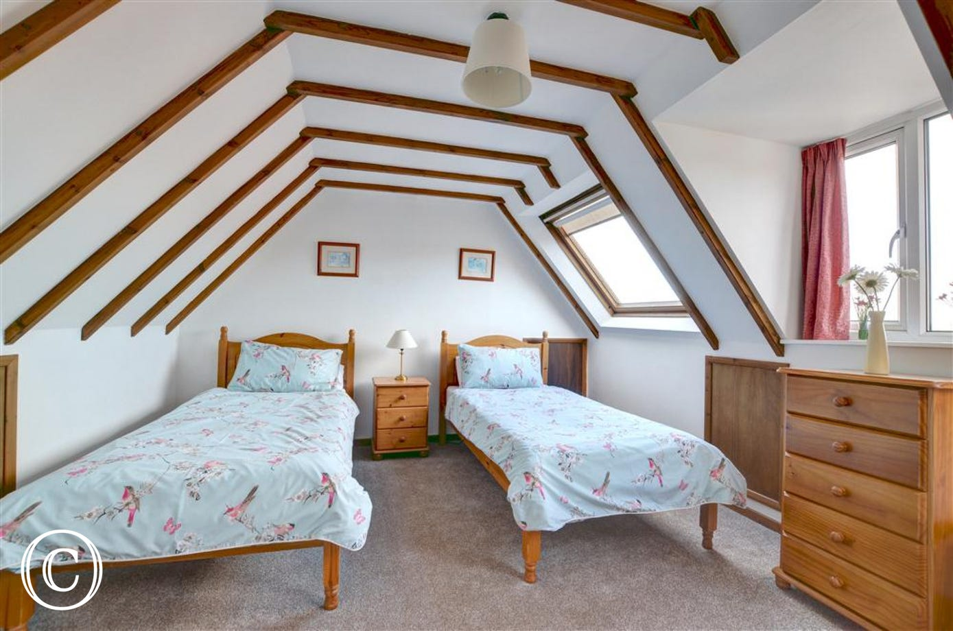 Second bedroom has two single beds and an open staircase.