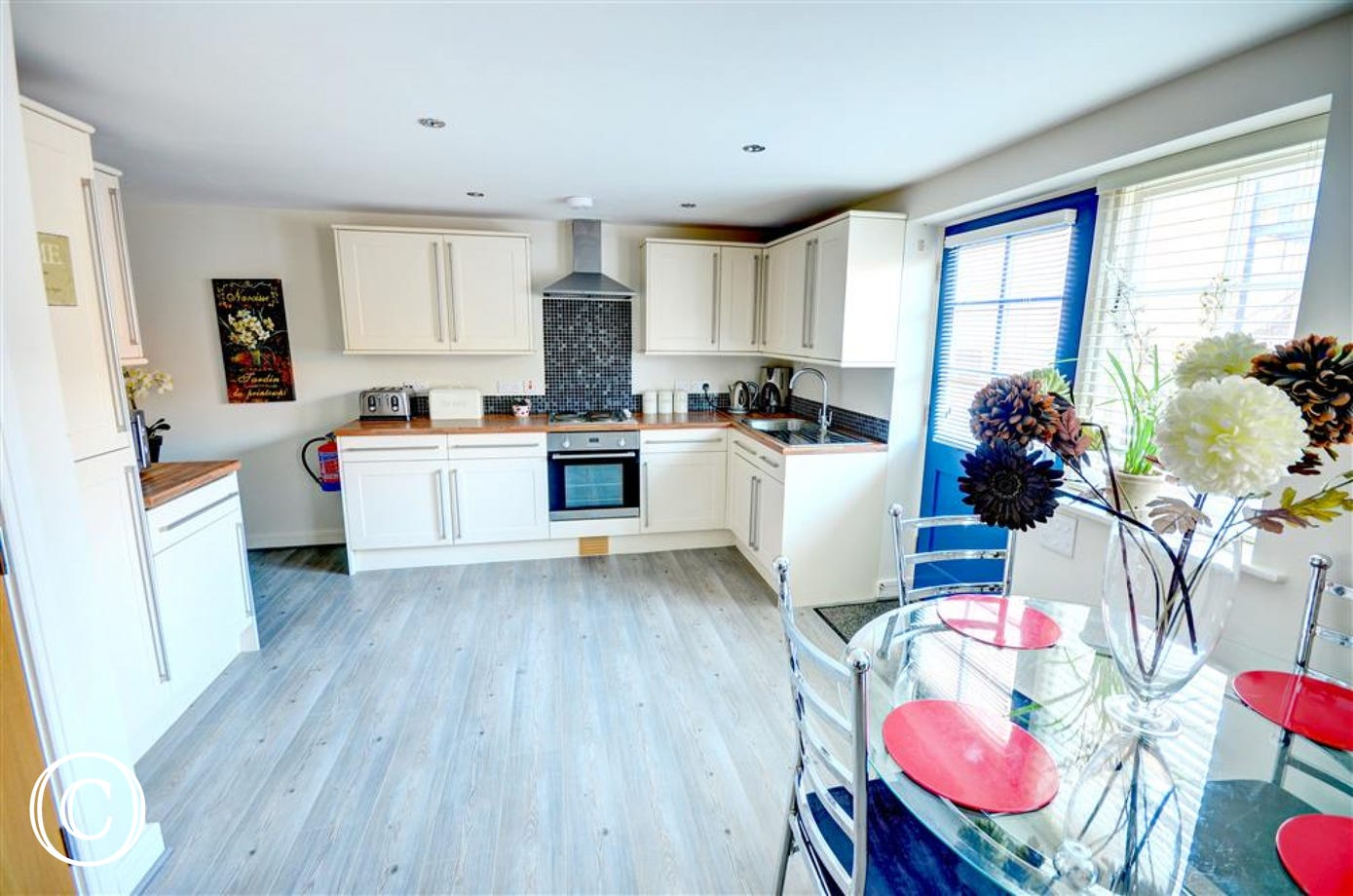 Open plan Kitchen area and door which leads to the front of the property.