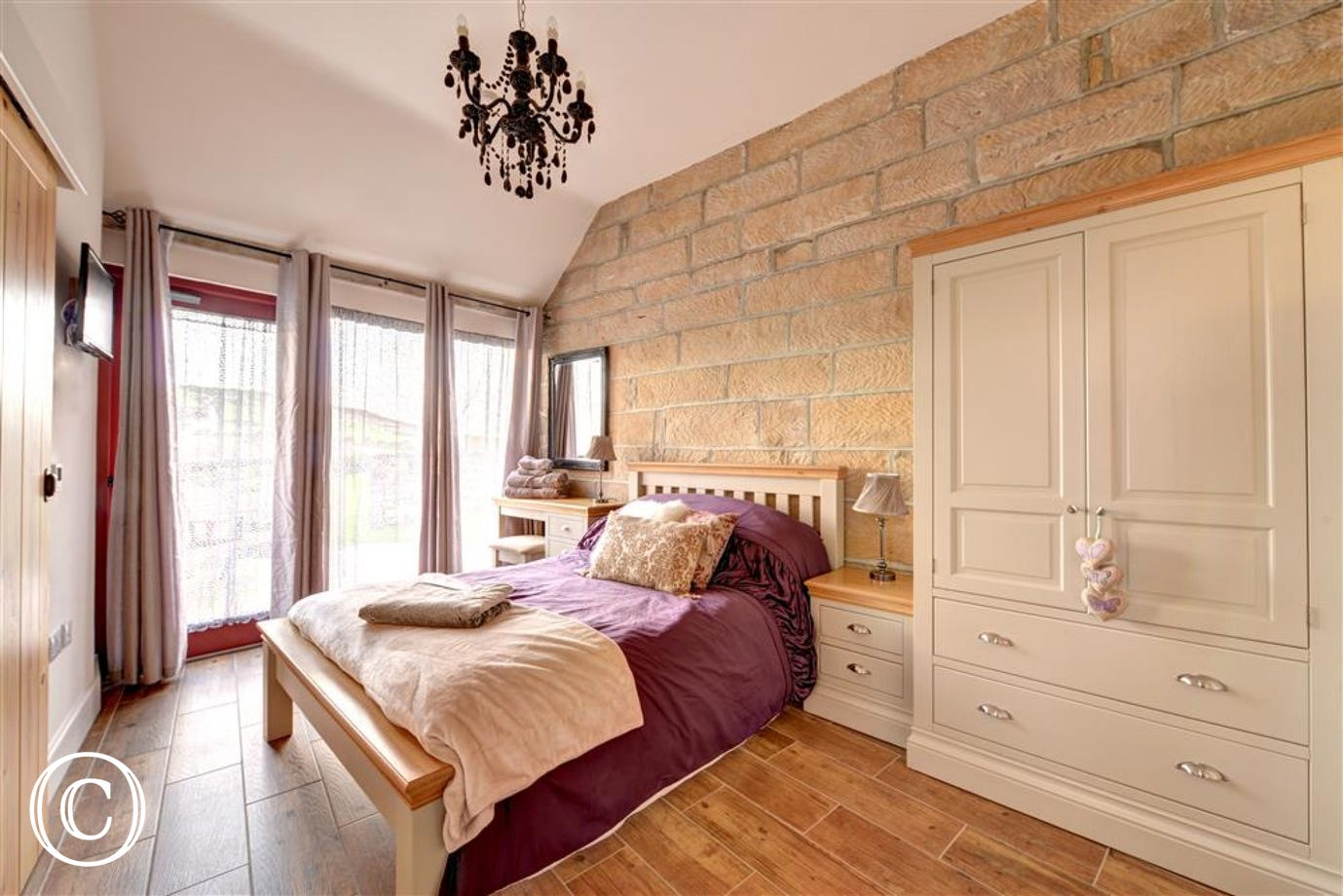 Bedroom 1 with double bed and floor to ceiling door and windows.
