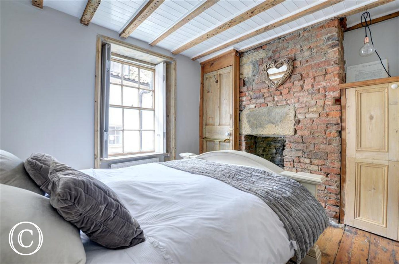 The double Bedroom includes a red brick stone wall.