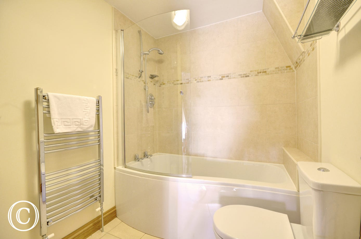 A modern bathroom suite with shower over bath.