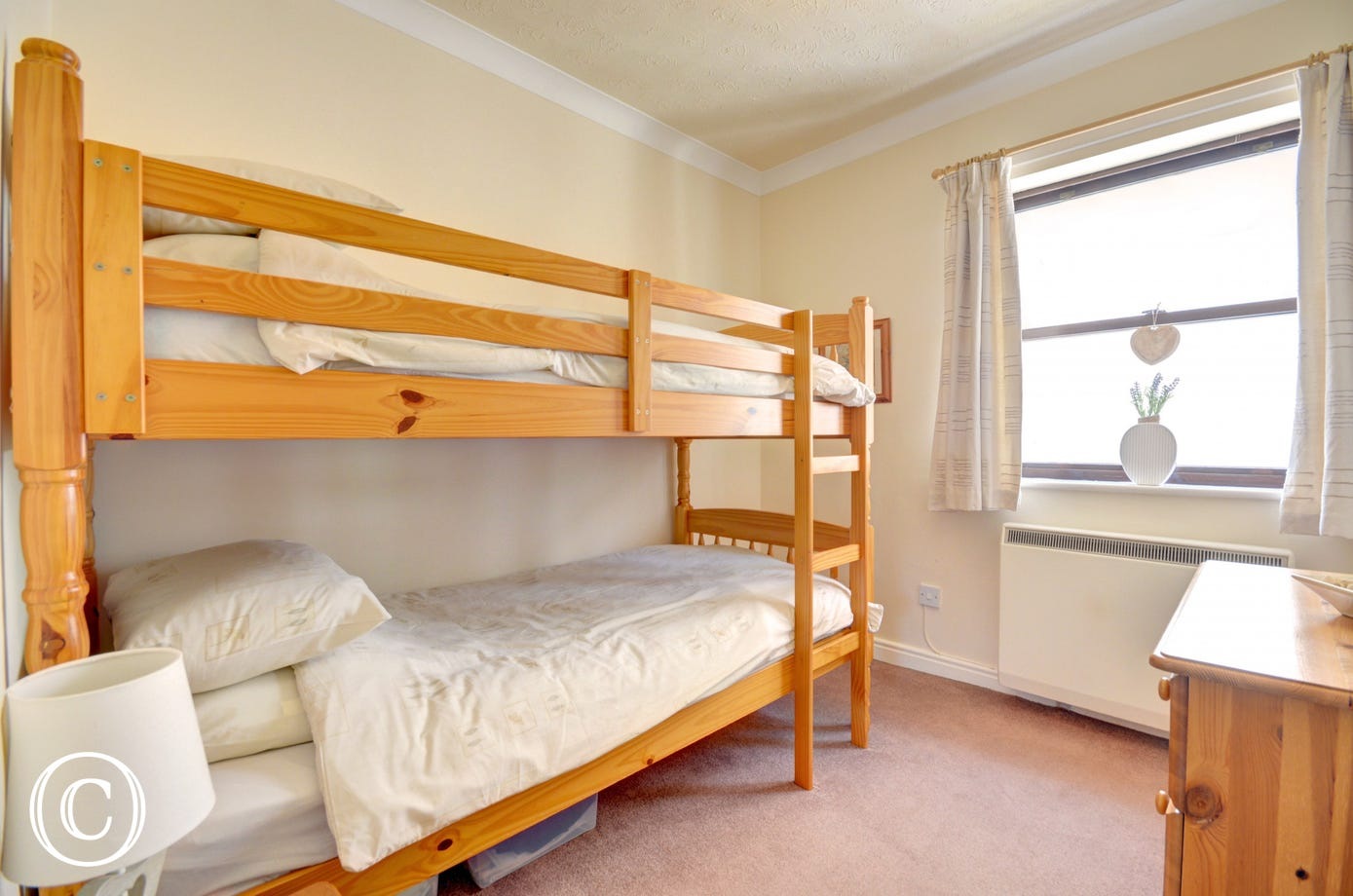 Twin bedroom with bunk beds and a chest of drawers for storage.