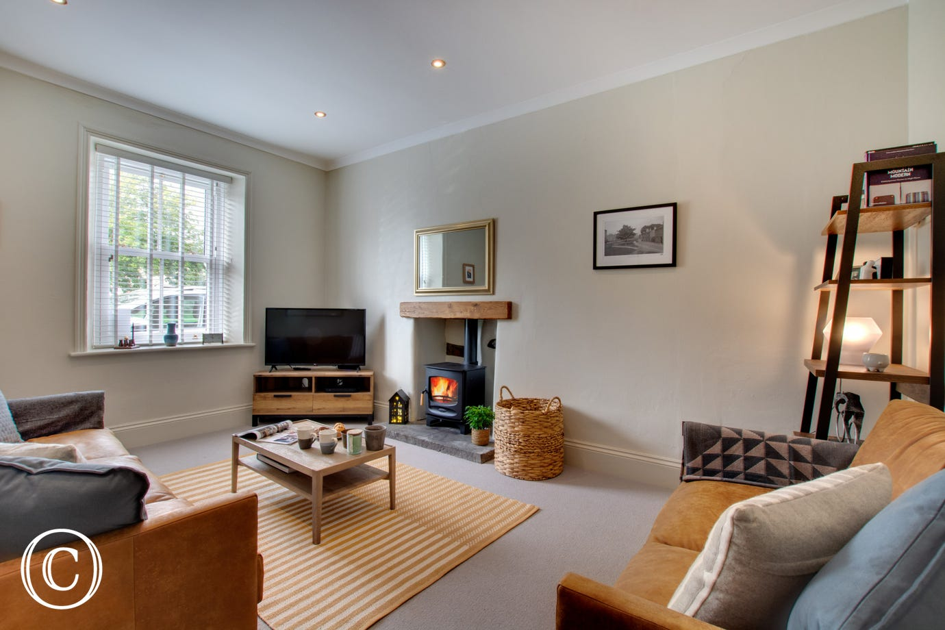 A spacious lounge with woodburning stove, ideal to cosy up in front of after a busy day exploring the Yorkshire Dales