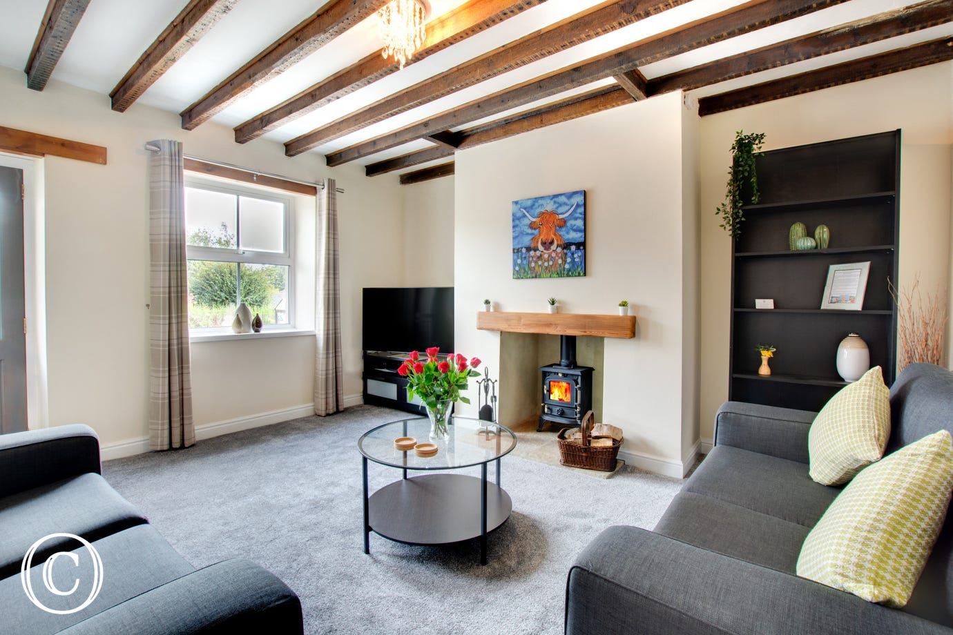 A cosy lounge with woodburning stove, large Smart TV, beamed ceiling, a fabulous comfortable lounge to relax in