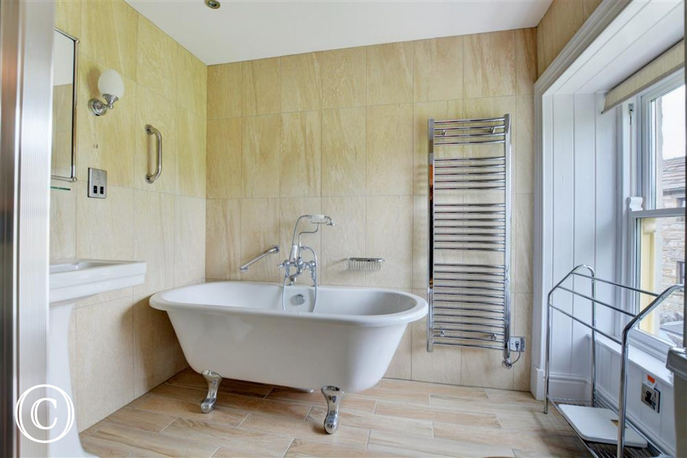 Light and spacious bathroom with roll top bath