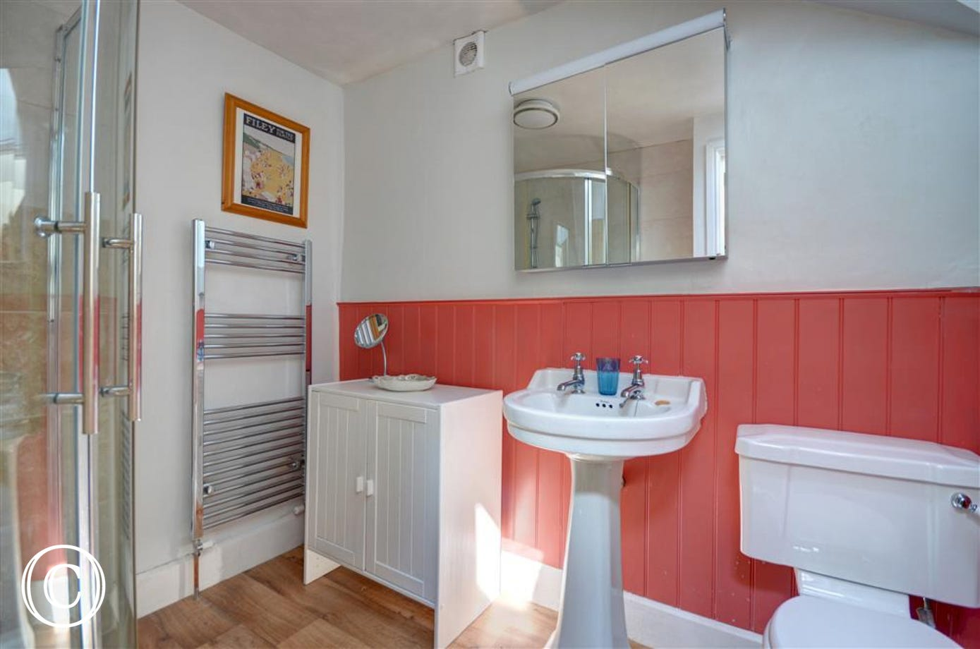 Pleasant family bathroom with a toilet, washbasin and some storage.