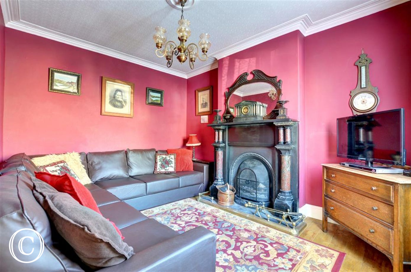 Cosy living room bursting with character, featuring an original fireplace.