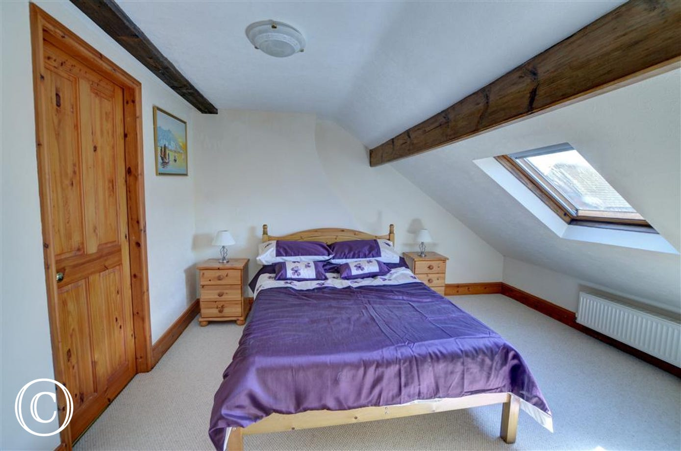 There are wooden beams and slightly sloping ceiling in Bedroom 3.