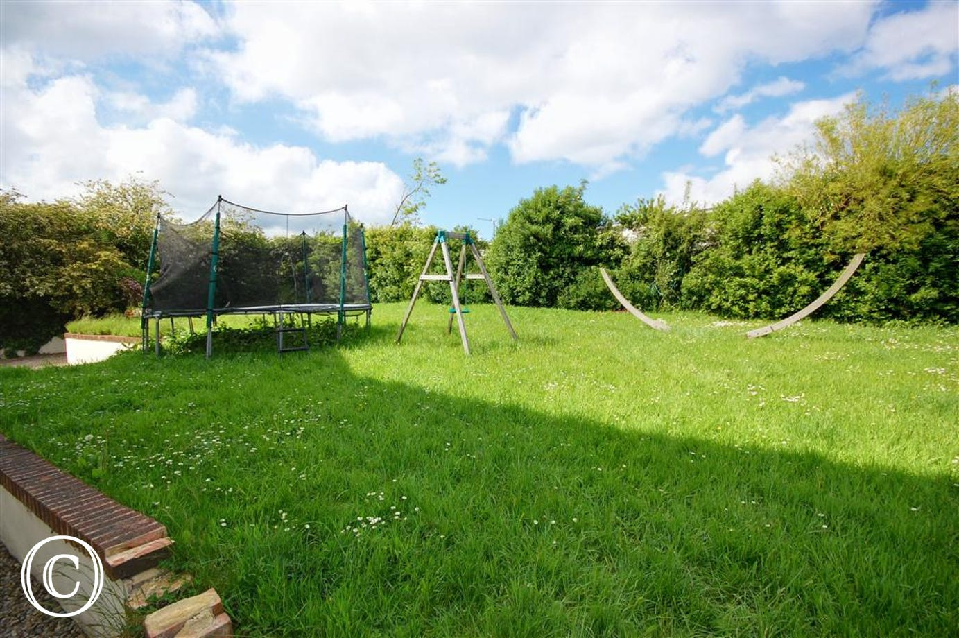 There is a Patio area and large Garden with children's play equipment to the rear of the property.