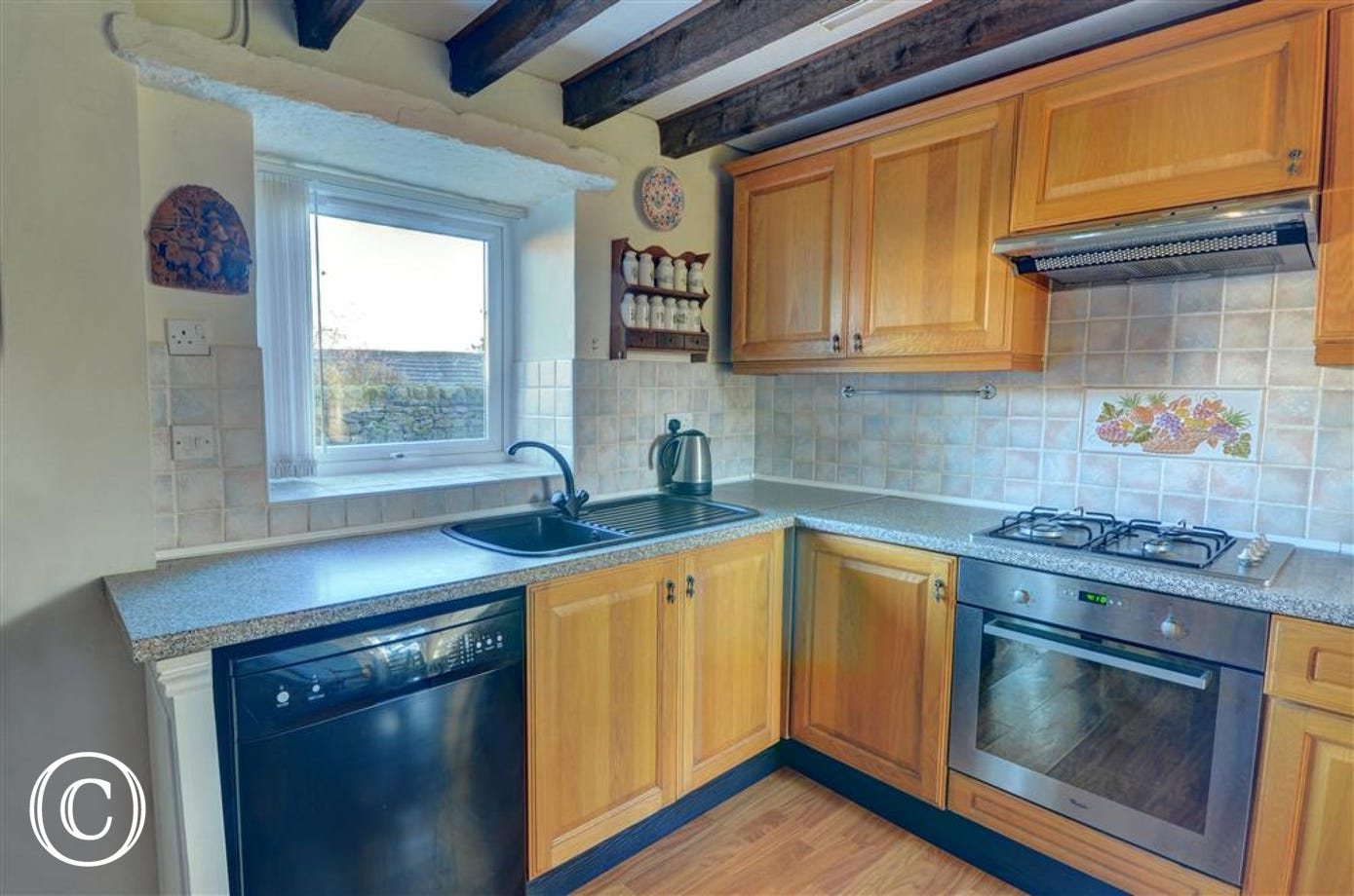 Spacious well equipped kitchen with original beams on the ceiling.