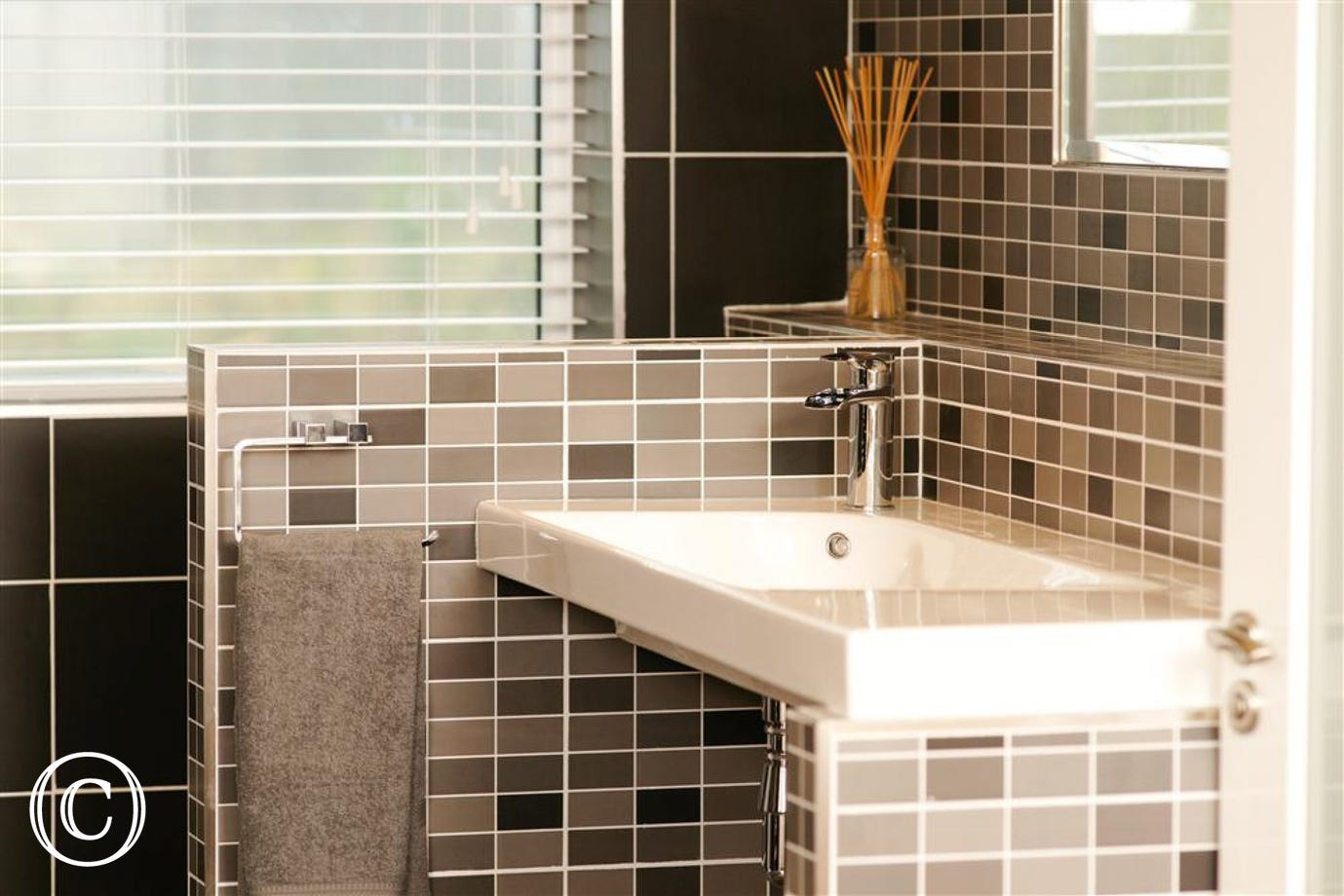 The colourful tiles and chrome fittings add a touch of class.