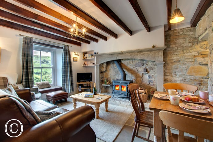A cosy lounge with woodburning stove and beamed ceiling
