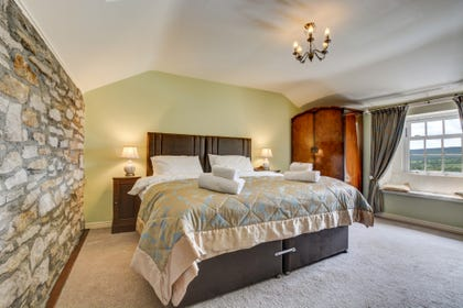 Spacious bedroom 2 with Zip & Link beds, window seat and feature stone wall