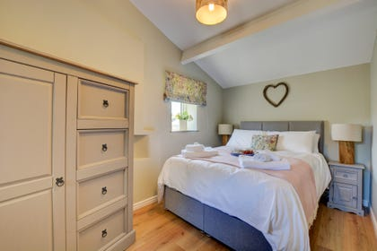 The bedroom complete with bespoke furnishings, overlooking the garden