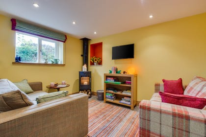 The comfortable lounge area with wood burning stove, stone floor with underfloor heating