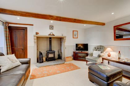 Spacious lounge with solid fuel stove and countryside views