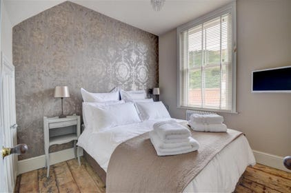 Bedroom 1 has a double bed with feather bedding and a Smart TV.