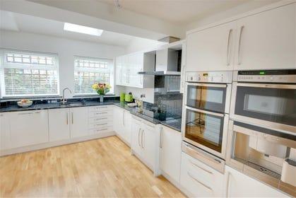 Modern fitted kitchen with all the gadgets including a built-in coffee maker.