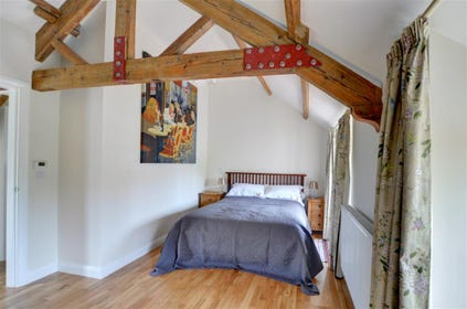 There is a king size bed and wooden beams in the bedroom.