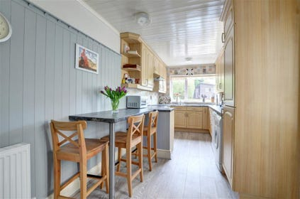 Spacious fitted Kitchen with breakfast bar and stools.
