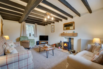 The spacious lounge complete with beamed ceilings, woodburning stove and quality furniture