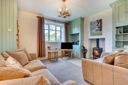 Lounge overlooking Bolton Castle, comfortable seating and a woodburning stove.