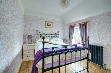 Pretty double Bedroom with double bed and characterful wooden floor.
