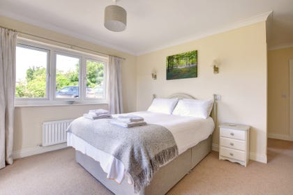 Master bedroom suite with french doors leading onto decking area which overlooks the gallops in Middleham and Pen Hill, en suite shower room.
