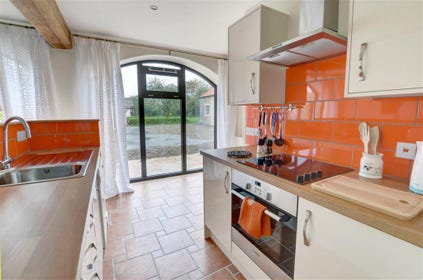 Kitchen has modern units and appliances.