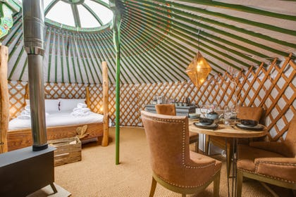 The cosy living area with woodburning stove at Barn Owl Yurt